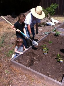 Big sister shovels as little sister supervises.