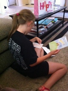 Lily (in her performance tee shirt) opening her card from Aunt Melody
