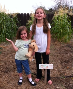 "Olivia (with Cupcake) and Lily with their ""Pupmkin Seeds"" sign."