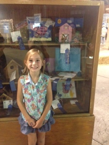 The blue ribbon winner in front of the display case.  Her pig is directly above her head, and the barn to the right is also hers.