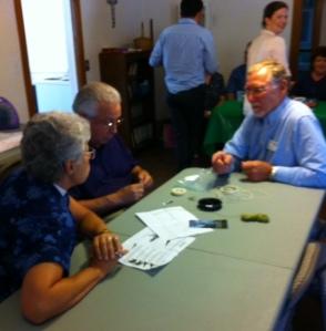 Mike Winn and Walt Bentley teaching Canon Kate Cullinane to tie flies.