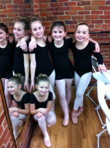 Little ballerinas waiting to begin.  Lily is standing up next to the mirror.