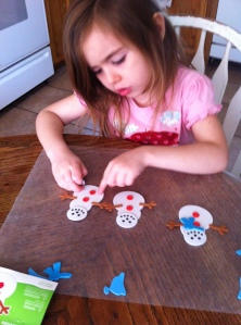 "Olivia concentrating on getting her snowman's buttons ""just so""."