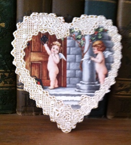 This heart-shaped card is of printed lace, hinged at the top.