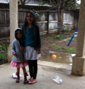 The girls all dressed for rain.  And yes, that is a puddle in the yard.